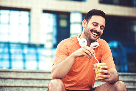 Young handsome man is enjoying fruit salad after jogging. Stock Photo