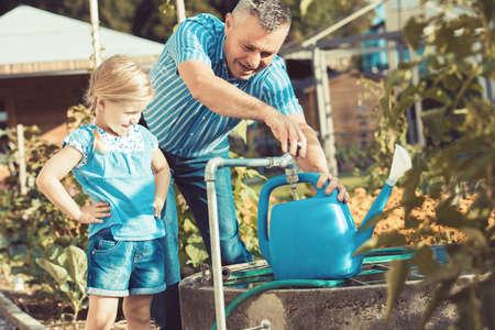 祖父は孫娘の花に水をまきます。 写真素材 - 85313238