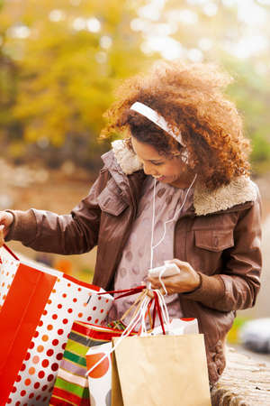 Beautiful woman enjoying autumn day in the par and shopping. Stock Photo