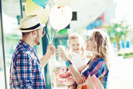 Happy family walking along the shopping mall with shopping bags and balloons. Banco de Imagens - 85656365