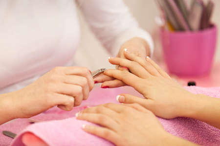 Woman hands receiving manicure and nail care procedure. Close up concept. Manicurist pushing cuticles on females nails. Stock Photo