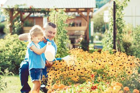 祖父は孫娘の花に水をまきます。 写真素材 - 85715291
