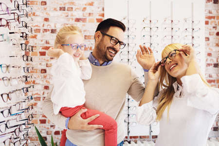 Happy family choosing glasses in optics store.