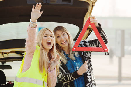 Beautiful young woman having trouble with car. They are waiting for help.  Stock Photo