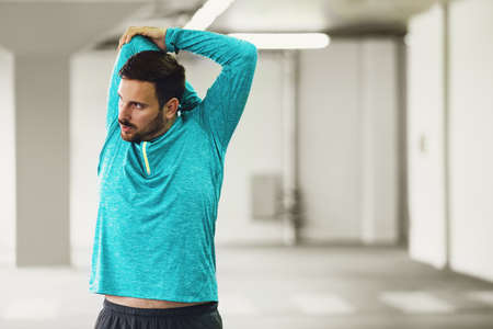 Young athlete man is exercising in garage. Stock Photo