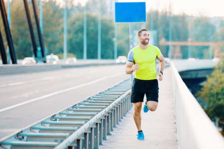 Early morning workout. Handsome man running on the bridge. Living healthy lilfestyle.
