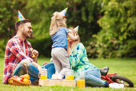 kids birthday party: Happy family of three celebrating birthaday party in the park. Stock Photo