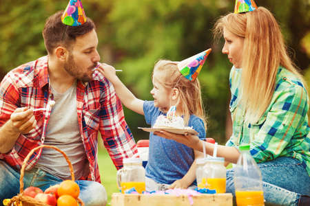 kids birthday party: Happy family of three celebrating birthaday party in the park and eating cake. Stock Photo
