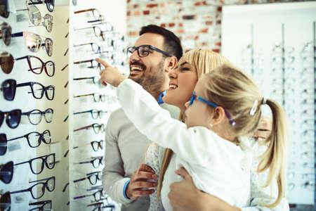 Szczęśliwa rodzina wybierając okulary w sklepie optyki. Zdjęcie Seryjne