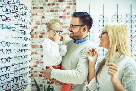 Happy family choosing glasses in optics store. Stok Fotoğraf - 87755456