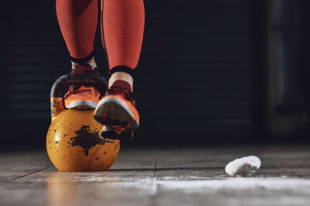 Young strong woman is training with kettlebell