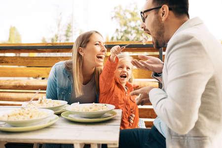 幸せな家族は、レストランでパスタを楽しんでいます。