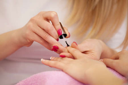 Woman hands receiving manicure and nail care procedure. Close up concept. Manicurist polishing females nails. Stock Photo