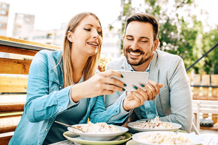Young couple enjoying restaurant and eating pasta.