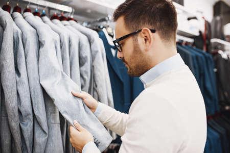Portret van knappe jonge man die kleding koopt in de winkel.