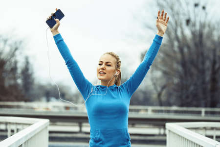 Young blonde woman exercising and listening music on the bridge. Stock Photo