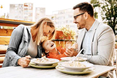 De gelukkige familie geniet van deegwaren in restaurant.