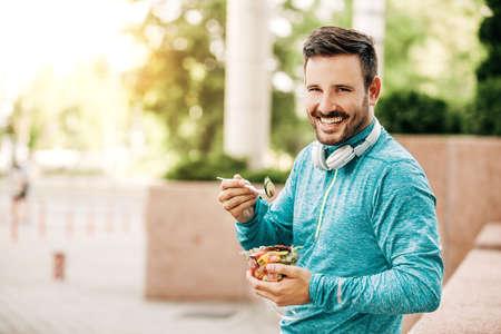 De jonge knappe man geniet van plantaardige salade na het joggen.