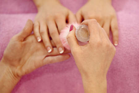 Woman hands receiving manicure and nail care procedure. Close up concept. Manicurist  brushing females nails.