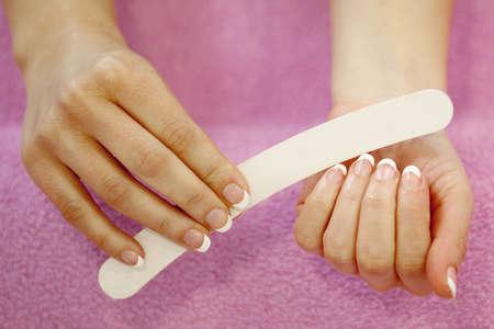 女性の手は、マニキュアとネイルケアの手順を受けました。クローズアップの概念。 写真素材