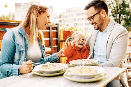 La familia feliz está disfrutando de pasta en restaurante. Foto de archivo - 89049169