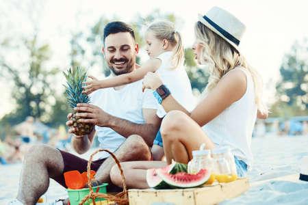 Happy family is enjoying beach and eating fruit. Stock Photo