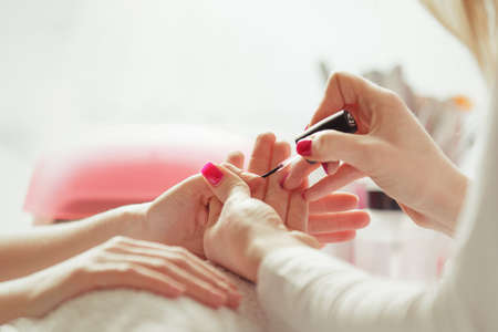 Woman hands receiving manicure and nail care procedure. Close up concept. Manicurist polishing on females nails.  Stock Photo