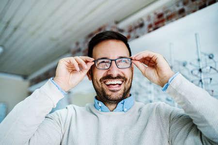 Mężczyzna wybiera okulary w sklepie optycznym.