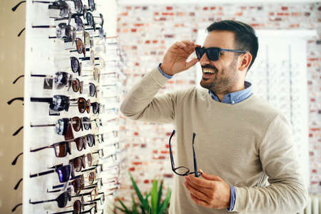 Man is choosing glasses in optics store.