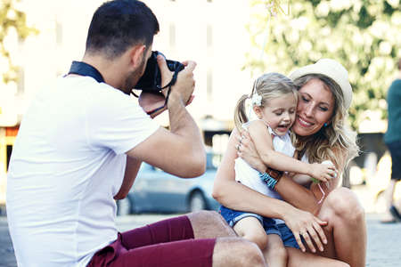 Young happy family is enjoying traveling and shooting photos. Stockfoto