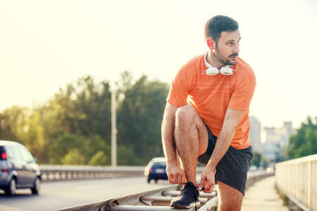 Young athlete man is exercising on the bridge. Banco de Imagens