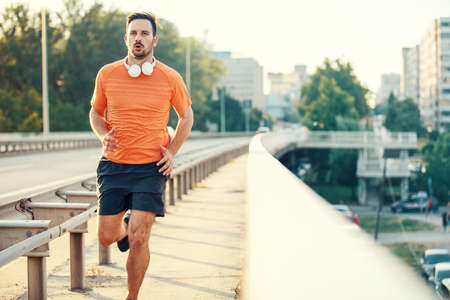 Young athlete man is exercising on the bridge. Stock Photo