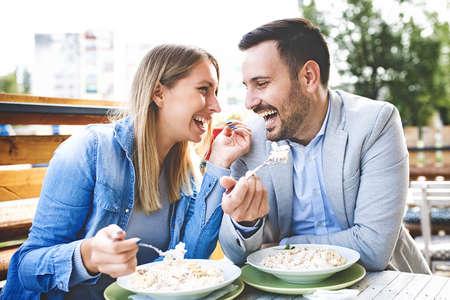 幸せなカップルはレストランでパスタを楽しんでいます。 写真素材