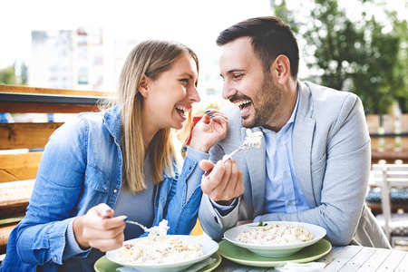 Happy couple is enjoying pasta in restaurant.