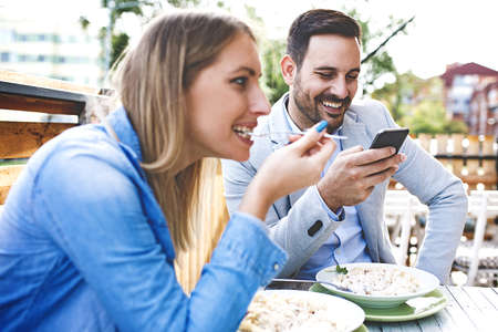 Happy couple is enjoying pasta in restaurant.