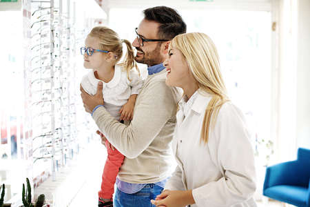 Four year little girl in optics store choosing glasses with her father. Ophtamologist helping.  Stock Photo