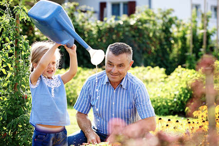 Grandfather is watering flowers with his granddaughter. 写真素材 - 94418322