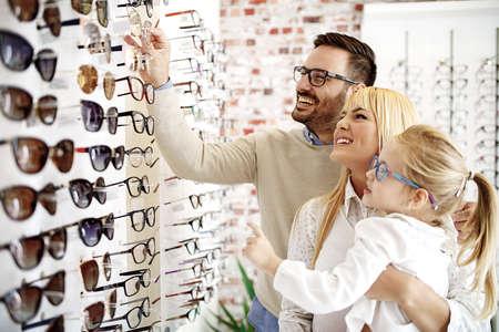 Menina de quatro anos na loja do sistema ótico que escolhe vidros com seu pai. Ophtamologist ajudando.