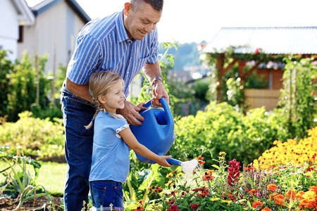 Grandfather is watering flowers with his granddaughter. 写真素材