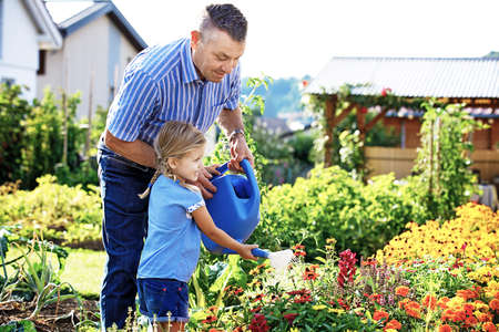 Grandfather is watering flowers with his granddaughter. 写真素材 - 94418371