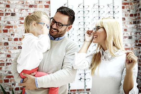 Four year little girl in optics store choosing glasses with her father. Ophtamologist helping.  Stok Fotoğraf