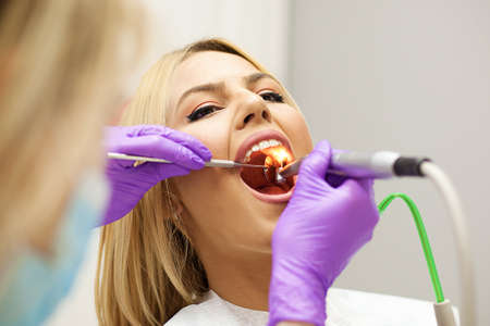 Female dentist and young woman patient in dentist office.