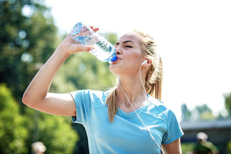 Young fitness woman having break after exercise and drinking water.