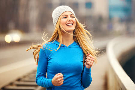 Young blonde woman is jogging early in the morning.