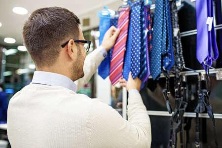 Portrait of handsome young man buying tie in the store. Foto de archivo