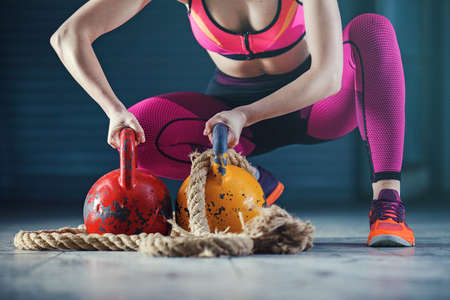 Young strong woman is training with kettlebell.