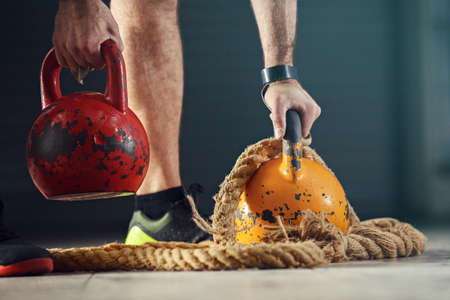 Young strong man is  training with kettlebell.