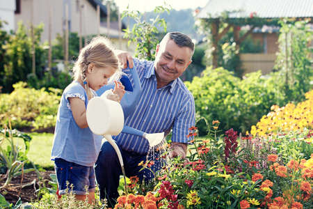 Grandfather is watering flowers with his granddaughter. 写真素材 - 103968270