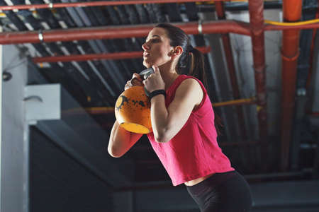 Young athelete woman is training in garage using kettle bell.