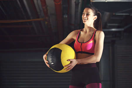 Young athlete woman is training in garage using ball. 스톡 콘텐츠